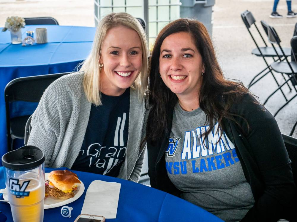 2 alumnae pose for a photo while enjoying delicious food at the tailgate